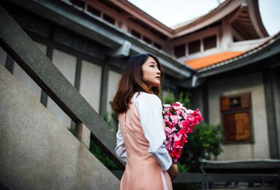Asian woman holding pink flowers